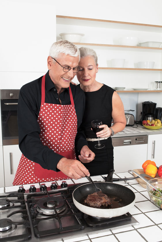 elderly man and elderly woman cook steak dinner